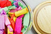 foto of jelly babies sugar  - Colorful candies are in a glass jar and a wooden lid - JPG
