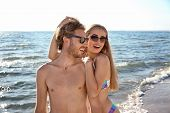 Happy Young Couple In Beachwear Spending Time Together On Seashore poster