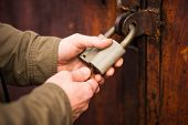 Mans Hands Close The Lock, Unlocking An Old Padlock poster