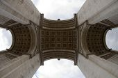 An upward view of the Arc de triomphe, the famous landmark and monument for the unknown soldier on the Champs Elisee in Paris, France on a cloudy day poster