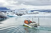 stock photo of amphibious  - An amphibious vehicle taking tourists for a cruise around the icebergs in the Jokulsarlon glacier lake - JPG