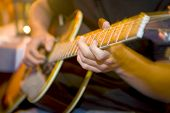 stock photo of acoustic guitar  - Fingers in motion on the frets of an acoustic guitar - JPG