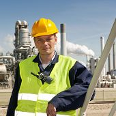 picture of retarded  - Portrait of an engineer in front of a petrochemical industry - JPG