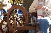 stock photo of olden days  - An elderly woman giving a demonstration of wool spinning - JPG