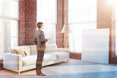 Businessman With Coffee Standing In His Luxury Living Room With Brick Walls, Concrete Floor, White S poster