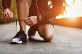 Cropped Image Of Hands Tying Shoelaces On Sneaker, Running Surface Background. Hands Of Sportsman Wi poster