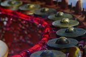 Closeup Of Old Brass Ancient Asian Musical Instruments In Semicircle Around The Position Of Musician poster