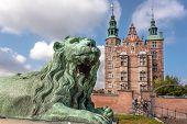 Tower Spires Over Lion Bronze Sculpture Guard At The Entrance Of Rosenborg Castle, Built In 17th Cen poster