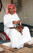 A Gulf Arab craftsman making small objects from dried reeds at the Doha Cultural festival. The focus
