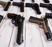 Firearms. Gun. Closeup The Gun Lies On A Wooden White Background. poster