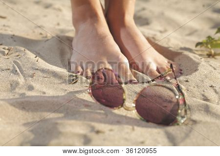 Woman feet with dark pedicure on the sand