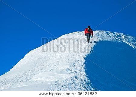 Lone male mountain climber on summit