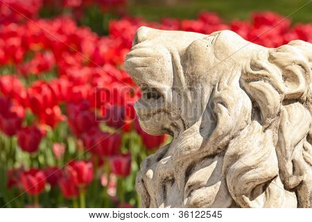 A Stone Lion Statue In A Yard Setting With Flowers