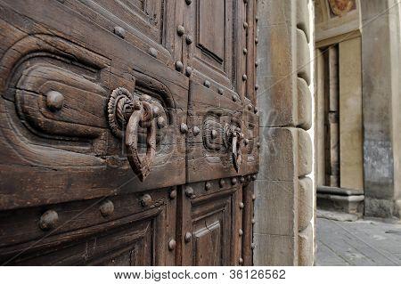 Old wooden door, knockers and stone made door-post