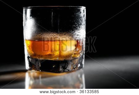 Closeup Misted Glass Of Whiskey In Backlight