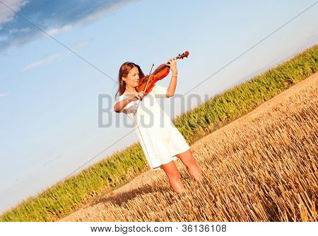 Young Woman Playing Violin Outdoors On The Field