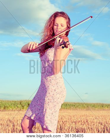 Redhead Woman Playing Violin Outdoors On The Field. Split Toning.