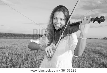 Young Woman Playing Violin Outdoors On The Field. Grayscale.