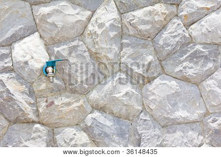 Faucet On The Background Wall Stone