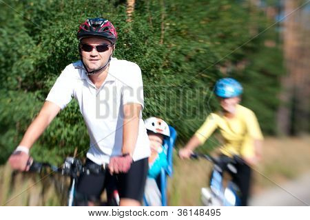 Family On The Bike In The Sunny Forest