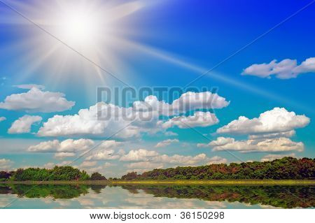 Lake And sun In The Sky Behind Wood.