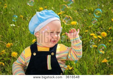 Child Sits On Grass And Looks On Soap Bubbles