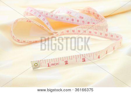 Tailor tapeline on cloth prepared for design desktop.