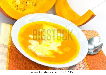 A Bowl Of Pumpkin Soup With Whipped Cream