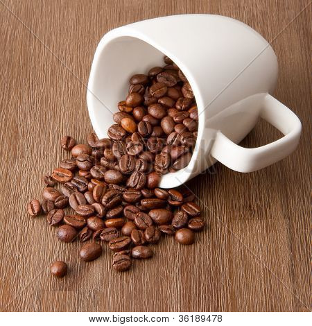 Coffee Cup And Spilled Coffee Beans
