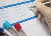 stock photo of phlebotomy  - Doctor ticking box on a blood test form. Narrow DoF focus on the tests being requested.