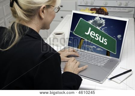 Woman In Kitchen Using Laptop