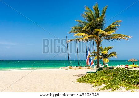 The tropical beach of Varadero in Cuba with coconut palms and colorful sailing boats