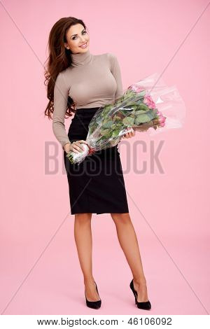 Beautiful elegant stylish woman with a large bouquet of cellophane wrapped roses in her hand received as a gift for Valentines Day or her anniversary