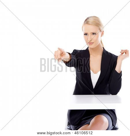 Sexy blond business woman sitting in front of desk isolated on white background