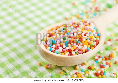 Colorful Sugar Sprinkles In Wooden Spoon On Tablecloth