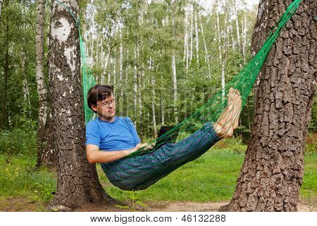 Young barefooted man in glasses with reclines in hammock at birchwood and works on notebook