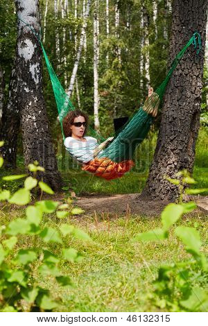Young barefooted woman in dark sunglasses lies in hammock outdoors and works on notebook