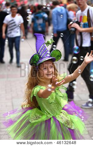 Happy little girl in fancy dress catching soap bubbles on the holiday of spring and bubbles Dreamflash