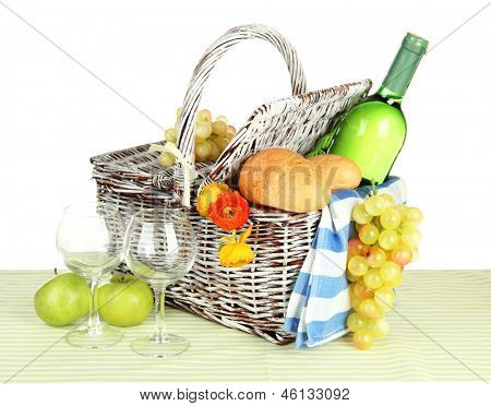 Picnic basket with fruits and bottle of wine, isolated on white