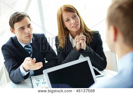 Confident business partners looking at young man during interview