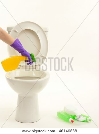 Woman hand with spray bottle cleaning a toilet bowl, isolated on white
