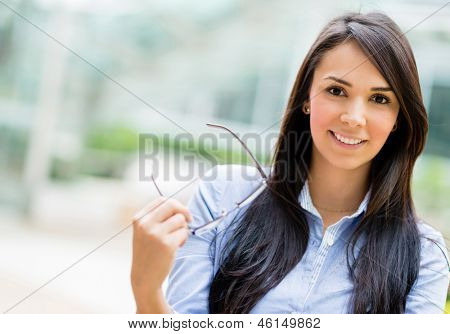 Casual business woman holding glasses and smiling