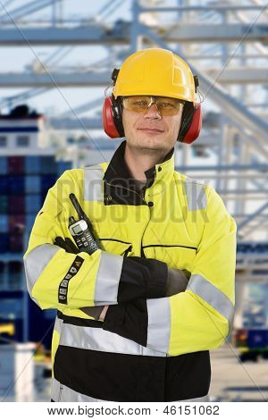Portrait of a confident docker, wearing all required personal protective equipment, posing in front of an industrial container terminal and harbor