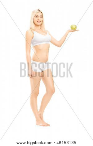 Full length portrait of a young beautiful woman in white cotton underwear holding a green apple isolated on white background