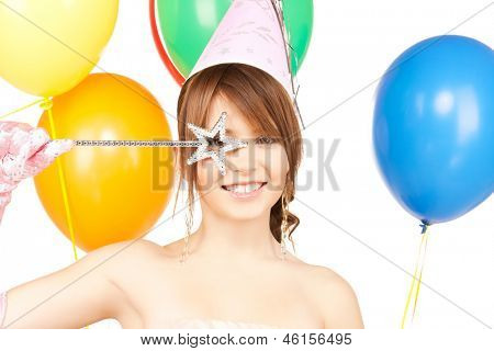 happy girl with colorful balloons in party cap and magic stick