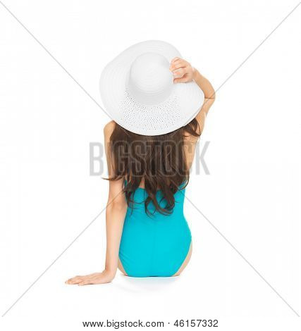 picture of model sitting in swimsuit with hat.