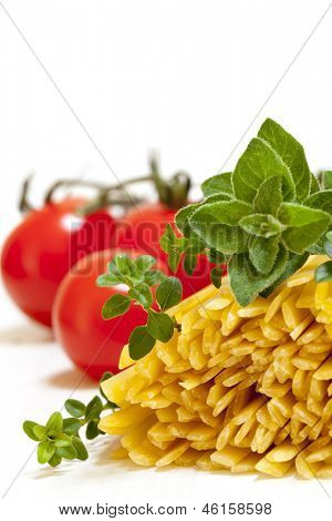 Uncooked fettucine pasta, with fresh thyme, oregano and tomatoes.