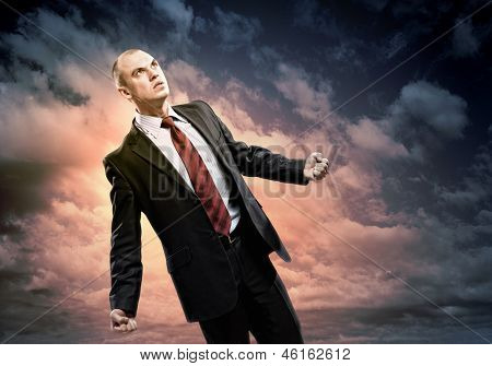 Image of young businessman in anger standing against cloudy background