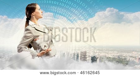 Image of young businesswoman holding alarmclock against illustration