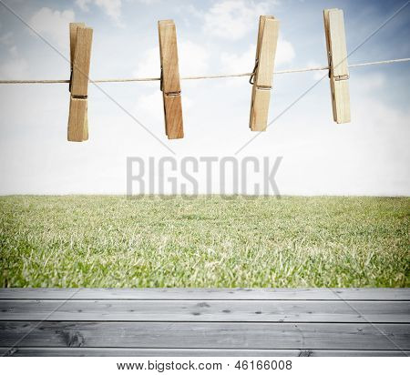 Clothespin on a laundry line outside above wooden boards with sky on the background
